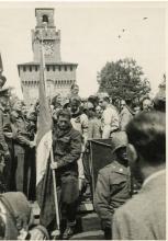 Esposizione della bandiera del C.L.N. all'arrivo in piazza Castello del corteo delle formazioni partigiane, cui prese parte anche la Divisione Flaim. Milano. 6 maggio 1945.